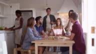 Young adult friends talking in kitchen make a toast, shot on R3D video