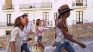Young adult friends walking in Ibiza, Spain, tracking shot, shot on R3D video