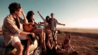 Young adult girl playing the guitar outdoor with friends video