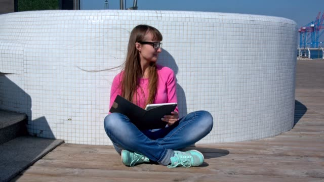 Young adult girl with her tablet pc outdoors video