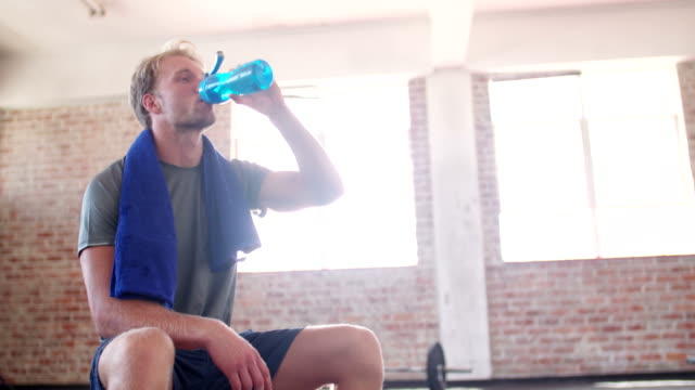 Young adult guy hydrating at the gym during gym training video