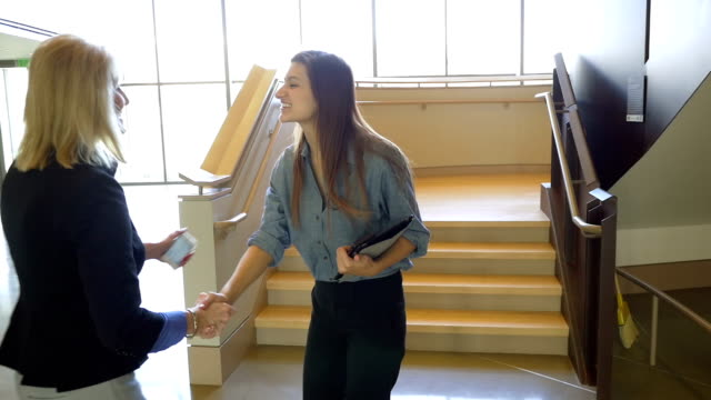 Young adult Hispanic businesswoman greeting mature female coworker in casual office video