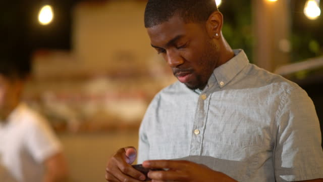 Young adult male at a party checking his smartphone video