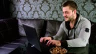 Young adult man sitting on the couch and working on a laptop at home video