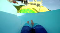 FPV FIRST PERSON VIEW POV: Young adult man sliding down the fun water slide at summer sunset in summer water park video