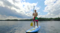 Young adult paddle boarding outdoors during summer video
