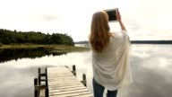 Young adult relaxes on jetty above lake, uses digital tablet video