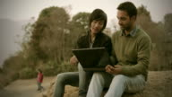 Young adult students using laptop in rural area video