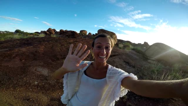 Young adult takes selfie portrait with spectacular landscape at sunrise video