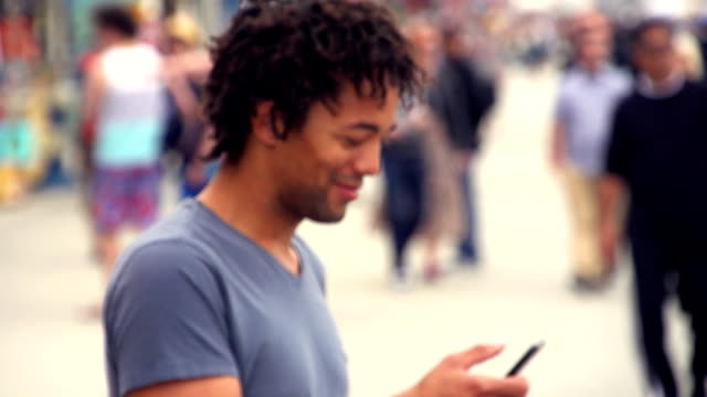 SLOW MOTION - Young Adult Using Phone on Venice Beach, Los Angeles. video