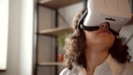 Young adult woman and a virtual reality headset. Girl using vr glasses video