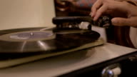 Young adult woman looking at record player in second hand store video