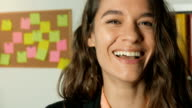 Young adult woman office worker looking directly at camera video