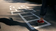 Young adult woman playing hopscotch outdoors video