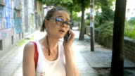 Young adult woman standing in front of a graffiti wall outdoors and talking on the phone video