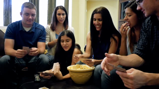 Young adult women playing cards with boyfriends, mother and sister video