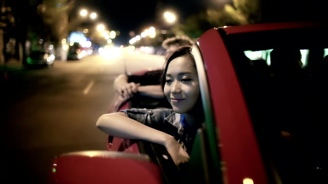 Young adults ride in a convertible on summer night video