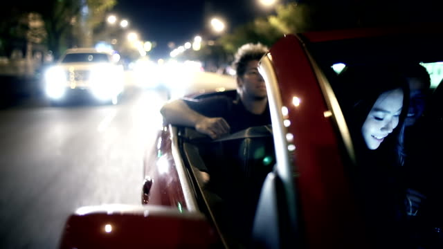 Young adults ride in convertible car at night. video