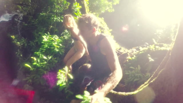 Young Adventure Couple Jumps Holding Hands off Cliff Into Water. Lush Green Jungle Waterfall. video