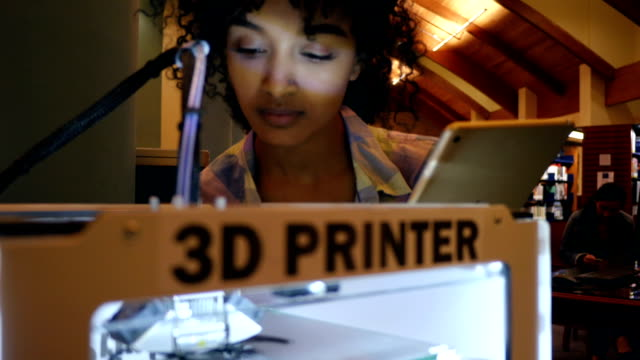 Young African American college student uses digital tablet to program 3D printer video