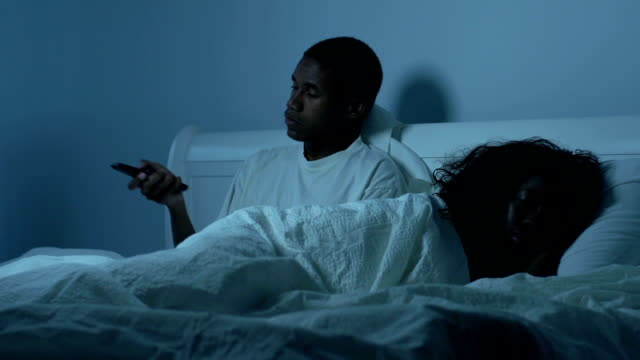 Young African American couple in bed with TV video