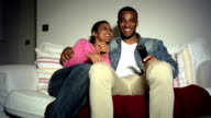 Young African American Couple On Sofa Watching TV Together video