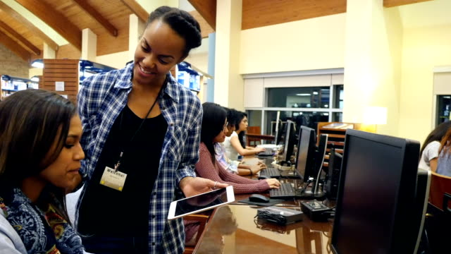 A young African American female librarian assists college or high school student in library computer lab video