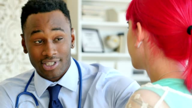 Young African American male doctor discusses diagnosis with a female patient video
