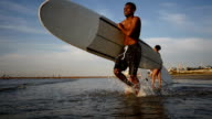 Young African American male surfer runs into the water with surfboard video