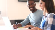 Young African American man and caucasian woman working together video