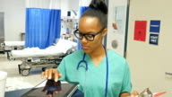 Young African American nurse is using a digital tablet to prepare for her next patient video