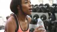 Young African American woman drinking water after exercising video