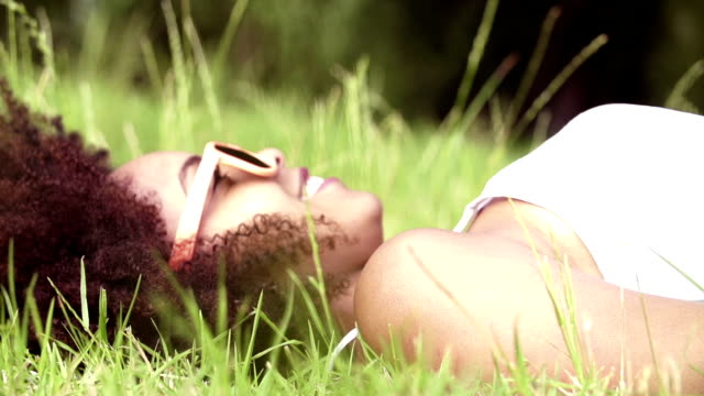 Young african american woman lying on green grass video