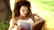 Young african american woman reading book in a hammock video