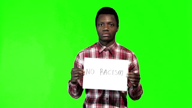 Young african man holds sign no racism video