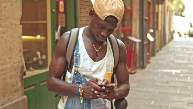 Young african man sending a text message on the mobile phone in the street video