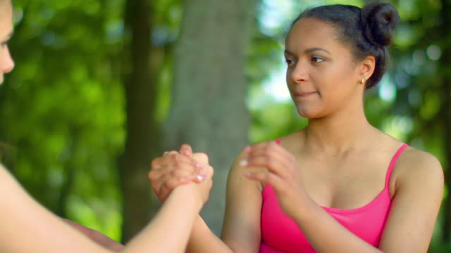 Young afro american woman doing stretching exercises with fit girl in park video