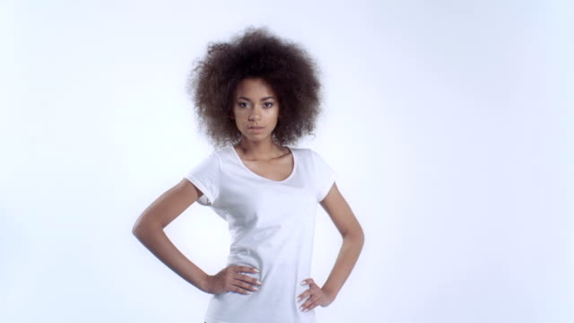 Young afro american woman in white t-shirt posing over white background. video