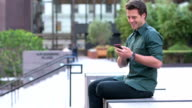 Young American man texting outdoors video