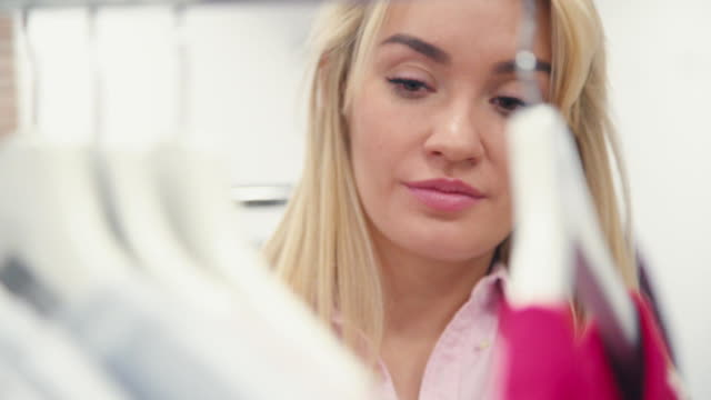 Young and attractive blond woman looking in clothes store video