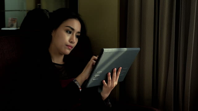 4K:A young and attractive woman playing with her tablet. video