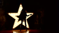 Young and beautiful rock girl playing the electric guitar, slow motion, silhouette video