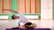 young and handsome man doing yoga video