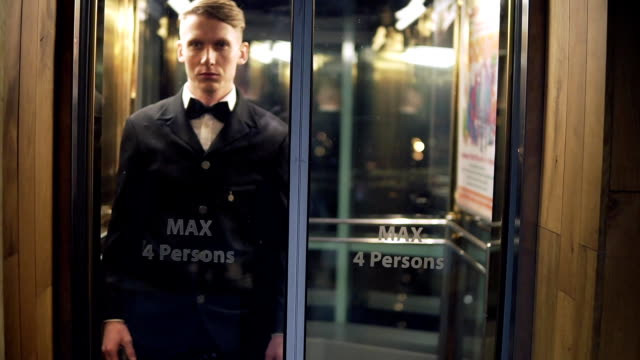 Young and successful businessman in a suit with a bow tie arriving and coming out of the Elevator with Glass Doors. video