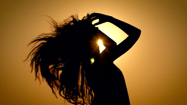 Young and unbelievebly beautiful woman alone, peacefully enjoying one of the last summer sunsets combing her hair back video