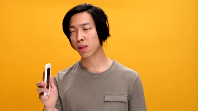 Young angry asian man talking by phone isolated over yellow background. video