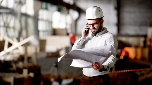 Young architect in protective helmet working in construction area. Supervisor of project holding blueprint and speaking on telephone. Foreman in white shirt discussing design of future apartment video