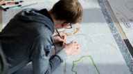 Young architect lies on floor and creates draft of building video