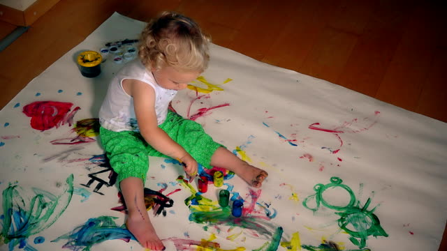 young artist kid girl painting on her hand and white paper on floor video