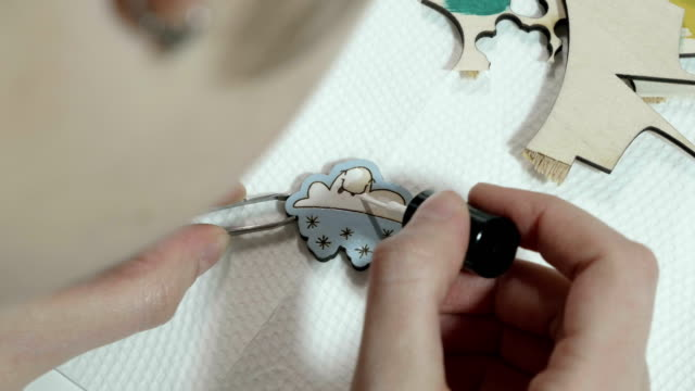 Young artist paints on wooden badge video